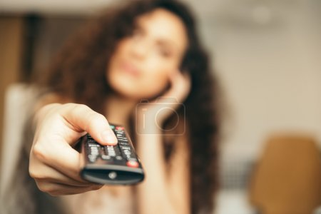 Girl holding a TV remote, changing the channel.