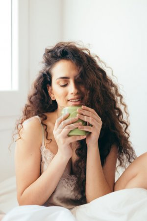 Photo for Sexy latin girl with curly hair drinking in bed with a cup in the morning - Royalty Free Image