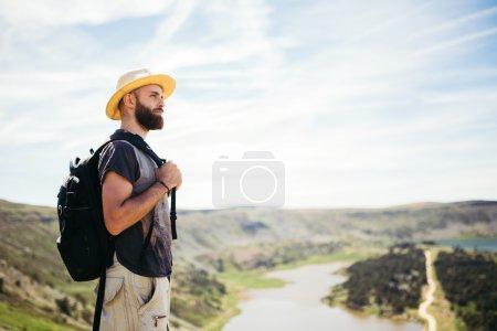 Photo pour Aventurier homme faisant de la randonnée dans une montagne avec lac - image libre de droit