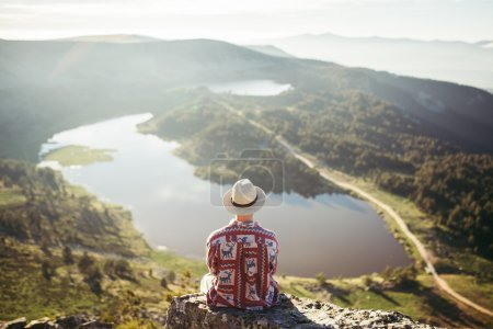 Man sitted in a rock looking
