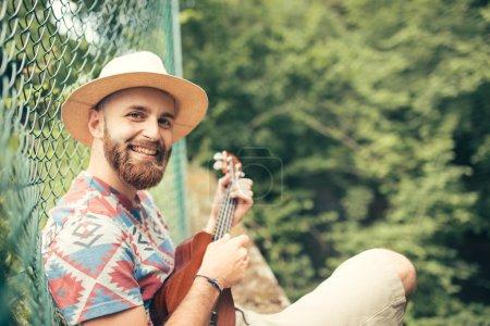 Man playing ukulele in nature