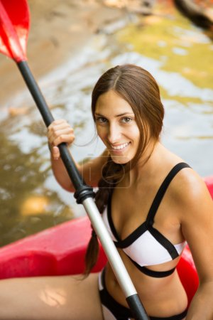 Brunette woman smiling in a canoe