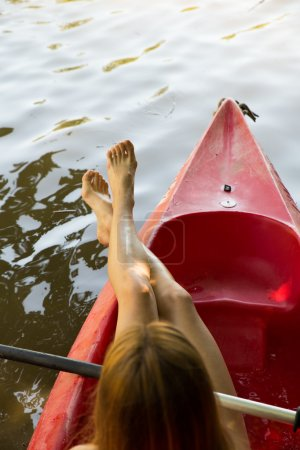 Woman feet on a red canoe