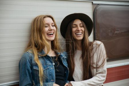 Two girls smiling supported in a van.