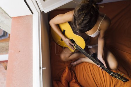 woman sitting on bed and playing guitar