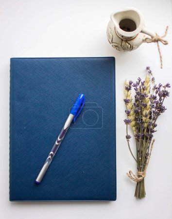 Copybook, pen and lavender isolated on white