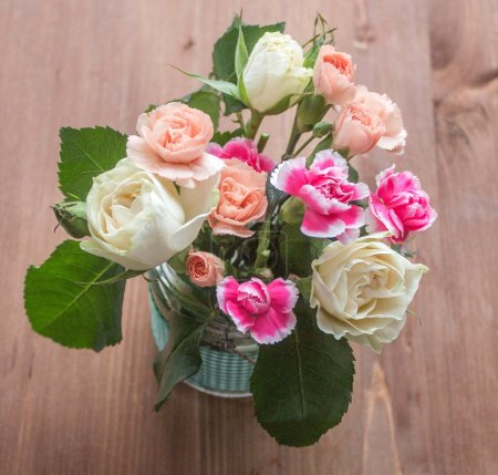 Bouquet of roses and carnations on wooden table