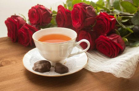 Red roses on wooden background with cup of tea