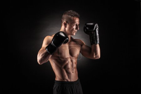 Photo for Muscular young man in boxing gloves and shorts shows the different movements and strikes in the studio on a dark background - Royalty Free Image