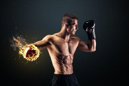 Photo pour Jeune homme musclé en gants et shorts de boxe montre les différents mouvements et grèves en studio sur un fond sombre - image libre de droit