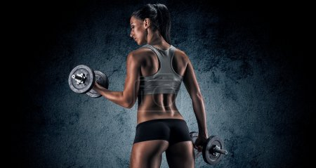 Muscular woman in studio on dark background