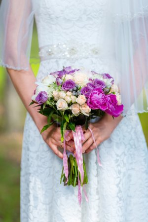 Bride in a white dress in summer green park with a wedding bouquet in hands