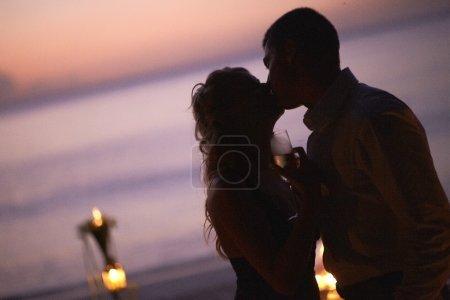 Photo pour Beau jeune couple embrassant sur le crépuscule, restant près de la table sur le dîner. Dîner de mariage sur le coucher du soleil. Style de vie se relatant sur l'île tropicale dans les Caraïbes ou Hawaii. - image libre de droit