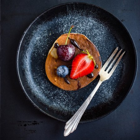 Pancake with fresh berries and chocolate sauce on  black plate