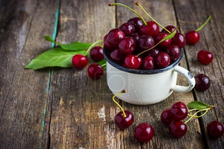 fresh cherries in enamel mug