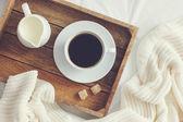 šálek kávy, smetany a hnědého cukru na dřevěný tác