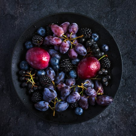 Fresh dark fruits and berries on black plate
