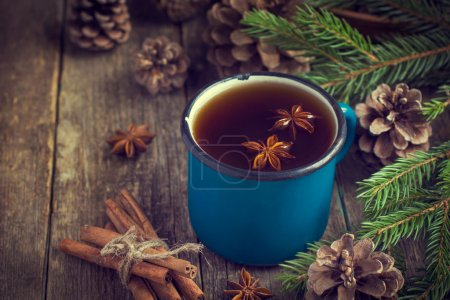 Hot spicy tea with anise and cinnamon in vintage blue enamel mug