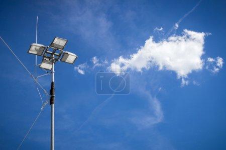 Photo pour Projecteur industriel avec fond bleu ciel et nuages - image libre de droit