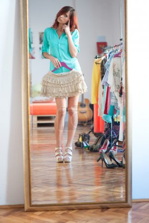 Photo for Girl trying wardrobe in dressing room - Royalty Free Image