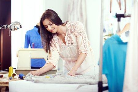 Female designer measuring textile material