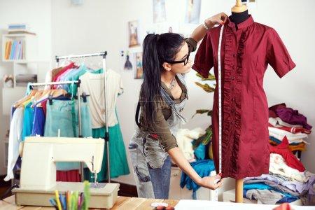Photo pour Jeune femme designer mesure robe - image libre de droit