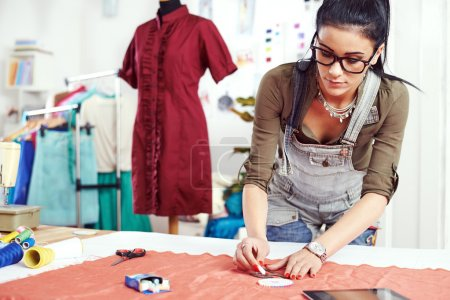 Young female designer measuring textile material...