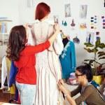 Постер, плакат: female designers working on a dress