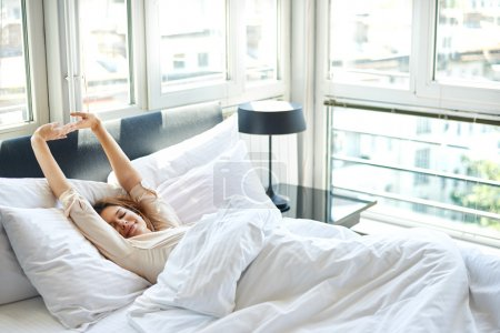 Photo for Woman stretching in bed after wake up - Royalty Free Image