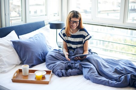 Photo for Breakfast in bed for young beautiful woman with glasses - Royalty Free Image
