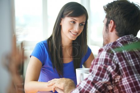 Smiling couple sitting in apartment