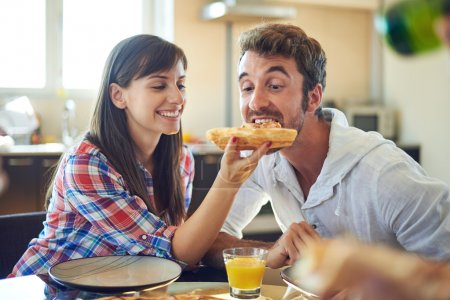 Girl feeding guy with piece of pizza
