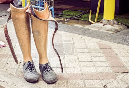 Photo for Old prosthetic legs set on a cement floor. Outdoor view - Royalty Free Image