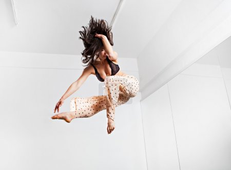 Jumping young woman on a trampoline. Indoors...