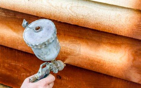 Photo pour Homme peint maison en bois avec pistolet pulvérisateur - image libre de droit