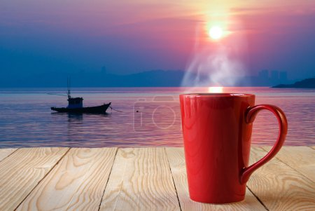 Photo for Red coffee cup with smoke on sun rise background - Royalty Free Image