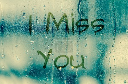 Natural water drops on glass window with the text I miss you