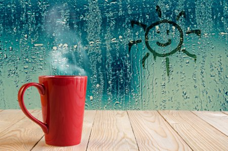 red coffee cup with smoke and sun sign on water drops glass wind