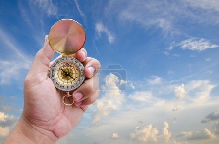 Man hand and compass with blue sky background