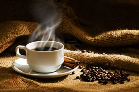 White coffee cup with smoke and coffee beans around