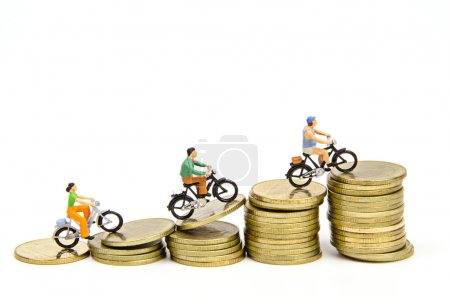 Miniature people ride on stack of coins