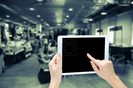 woman hand holding the phone tablet on blur market background