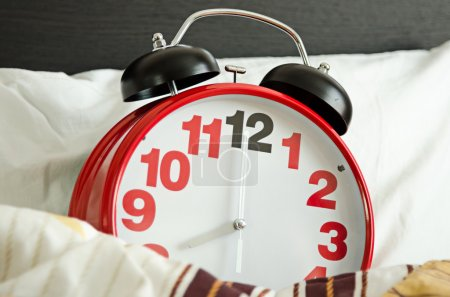 Alarm clock sleeping in bed