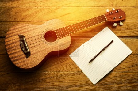 ukulele guitar with blank notebook and pencil