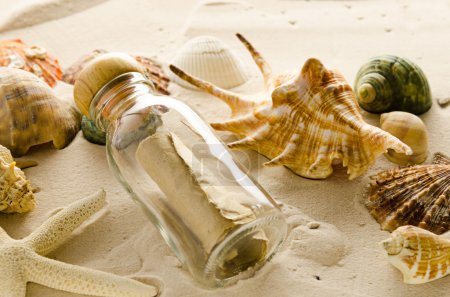 Photo for Bottle letter and sea shells on sand background - Royalty Free Image