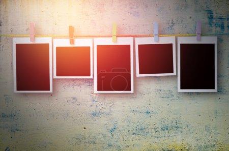 Photo pour Cadres photo noirs vides suspendus avec des pinces à linge sur fond de mur de pierre dans le ton vintage - image libre de droit