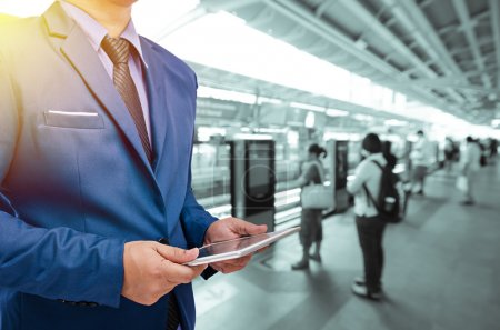 business man holding tablet with blurry train station background