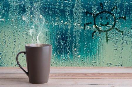 Photo pour Tasse de café brun avec fumée et signe du soleil sur gouttes d'eau fond de fenêtre en verre - image libre de droit