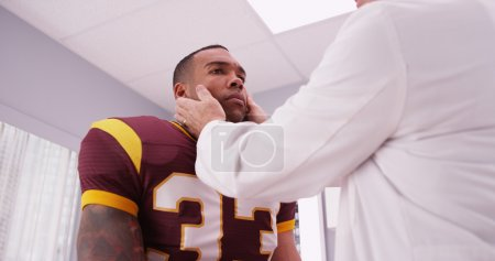 Mid aged doctor checking football player's sports neck injury