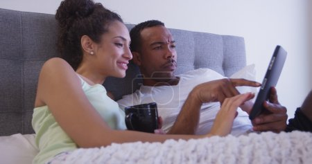 Early morning couple looking at tablet computer in bed and drinking coffee